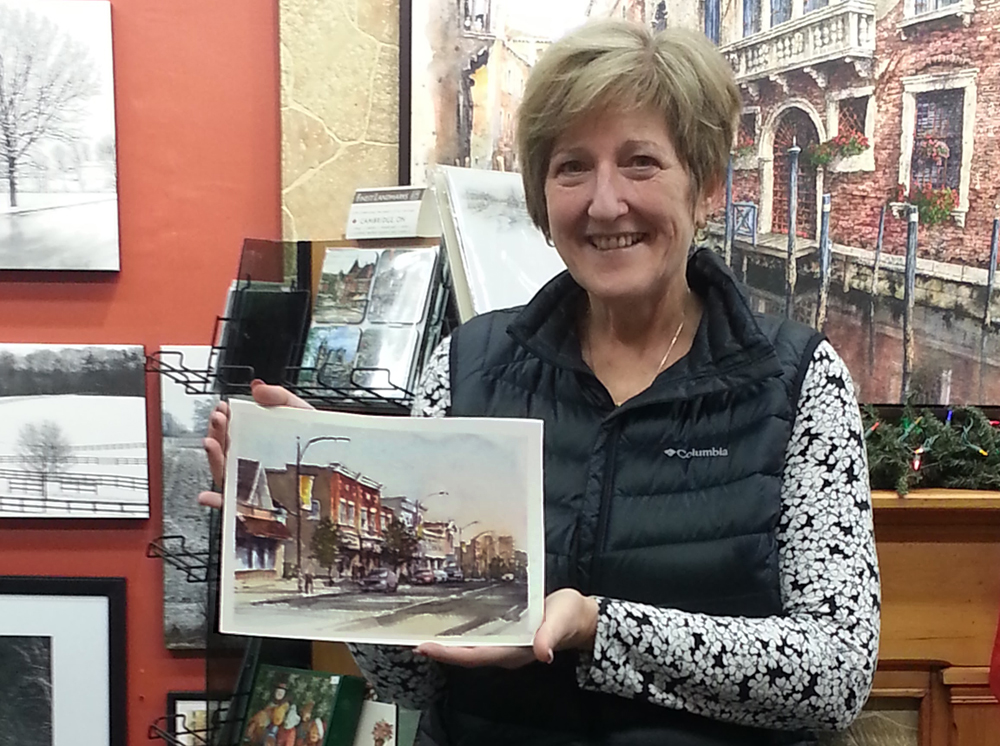 Gallery customer with the commissioned portrait of her childhood home in Preston Ontario