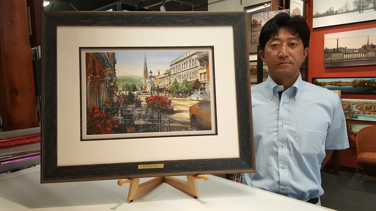 Original Painting by Alex Krajewski Walking Down Main Street custom framed by Krajewski Gallery and presented as a corporate gift to a local car company