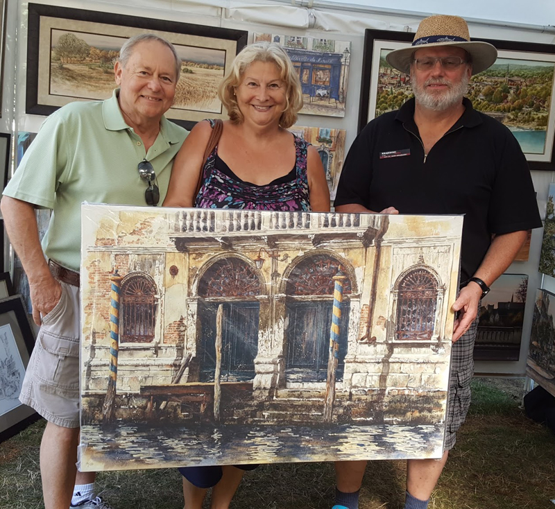 Canadian artist Alex Krajewski at a show with happy customers